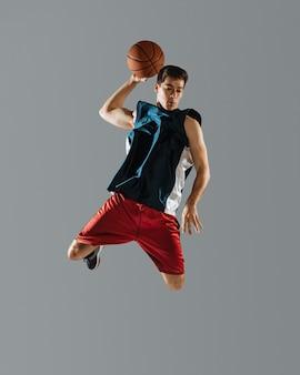 Junger mann, der beim basketballspielen springt