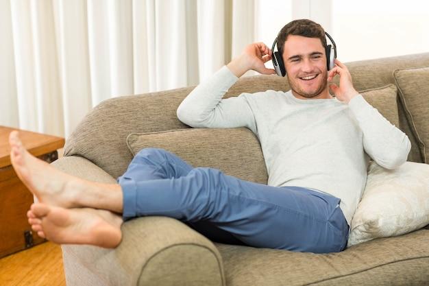 Junger mann, der beim hören musik mit kopfhörern im wohnzimmer entspannt sich fühlt