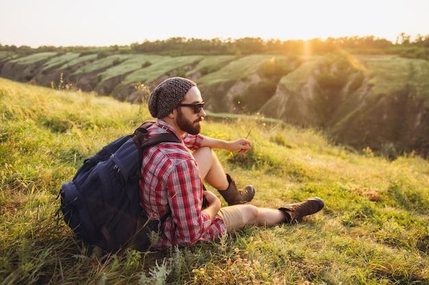 Junger mann, der beim picknick im sommerwald zusammen spazieren geht?