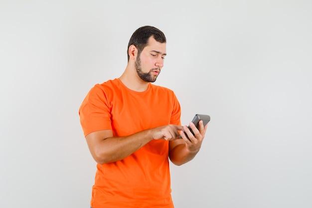 Junger mann, der berechnungen auf rechner im orange t-shirt macht und beschäftigt schaut, vorderansicht.