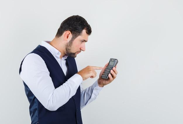 Junger mann, der berechnungen auf taschenrechner in hemd, weste macht und beschäftigt schaut