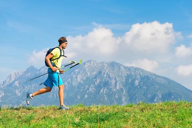 Junger mann, der berg der körperlichen aktivität übt und mit stöcken läuft