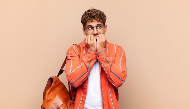 Junger mann, der besorgt, ängstlich, gestresst und ängstlich aussieht, fingernägel beißt und nach seitlichem kopierraum sucht. studentisches konzept