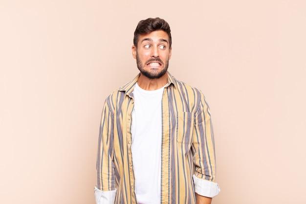 Junger mann, der besorgt, gestresst, ängstlich und ängstlich aussieht, in panik gerät und zähne zusammenbeißt