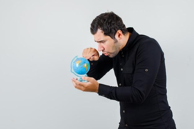 Junger mann, der bestimmungsort auf globus im schwarzen hemd wählt