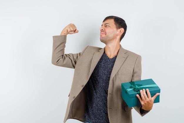 Junger mann, der blaue geschenkbox hält, während er seine armmuskeln in der graubraunen jacke zeigt und glücklich schaut. vorderansicht.