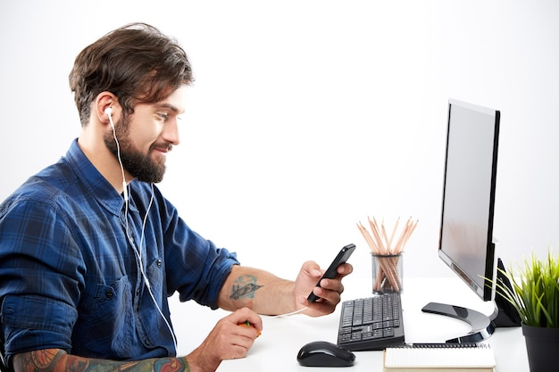 Junger mann, der blaues hemd sitzt, das mit laptop sitzt und zur musik, freiberufliches konzept, porträt, online-job, entspannen, blick auf das mobiltelefon auflistet.