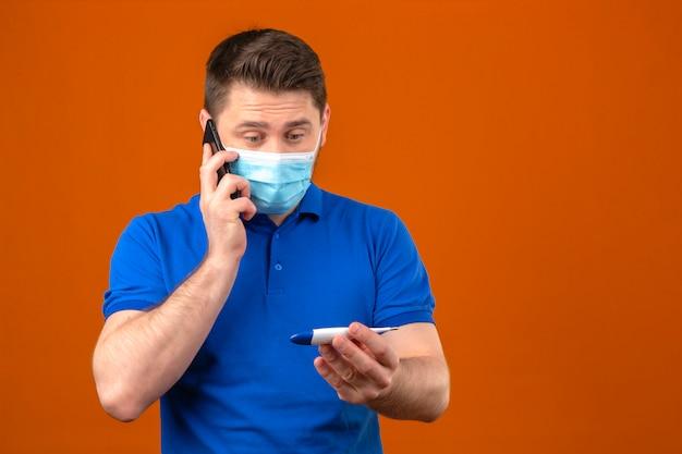Junger mann, der blaues poloshirt in der medizinischen schutzmaske trägt, die das digitale thermometer in der hand betrachtet, die auf handy spricht, das nervös und besorgt über isolierte orange wand sieht