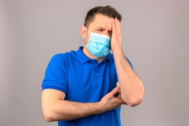 Junger mann, der blaues poloshirt in der medizinischen schutzmaske trägt, die unwohl und krank steht und mit hand auf kopf steht, die unter kopfschmerzen über isolierter weißer wand leidet