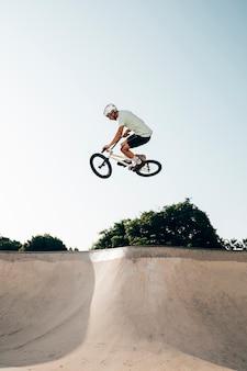 Junger mann, der bmx fahrrad auf eine rampe fährt