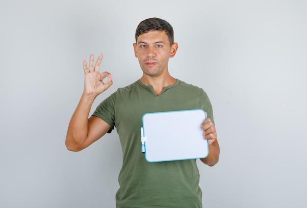 Junger mann, der brett hält und ok zeichen in der vorderansicht des grünen t-shirts der armee tut.