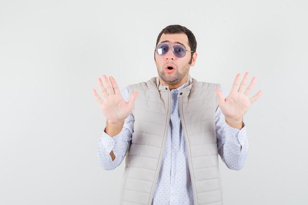 Junger mann, der brille aufsetzt, während hände in der übergabe in beige jacke und mütze erhebt und ängstlich, vorderansicht schaut.