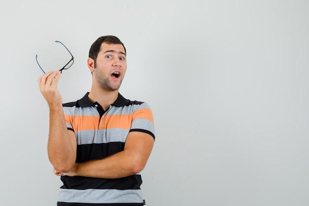 Junger mann, der brille hält, während er etwas im t-shirt spricht und gesprächig aussieht. platz für text