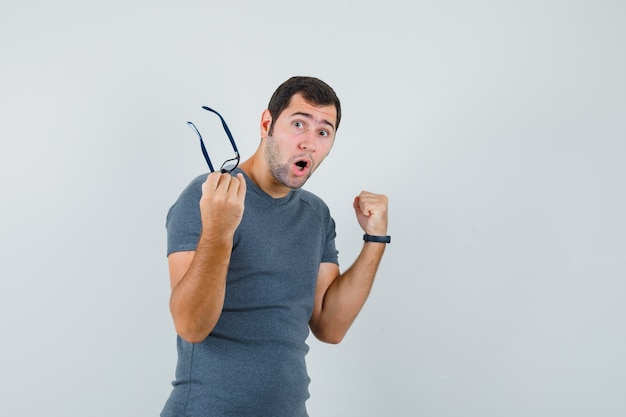 Junger mann, der brille im grauen t-shirt hält und glückliche vorderansicht schaut.