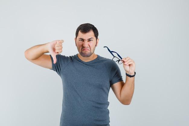 Junger mann, der brille im grauen t-shirt hält und unzufrieden schaut, vorderansicht.