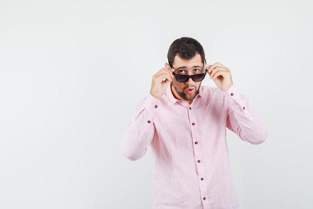 Junger mann, der brille im rosa hemd abnimmt und überrascht schaut