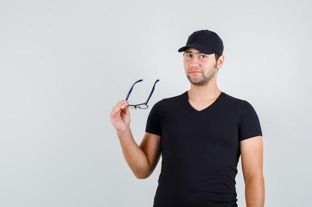 Junger mann, der brille im schwarzen t-shirt hält