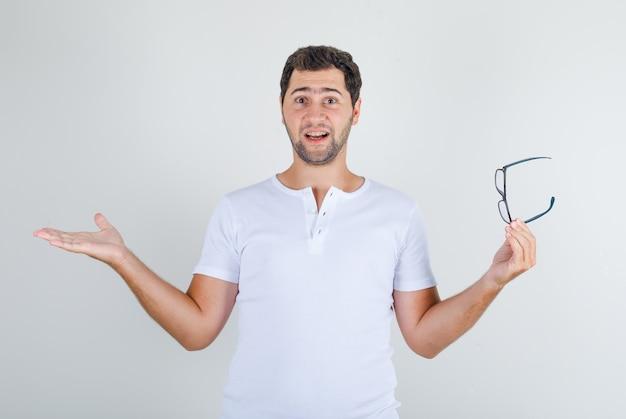 Junger mann, der brille mit offenen armen im weißen t-shirt hält und glücklich schaut