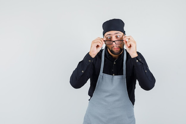 Junger mann, der brille mit zusammengekniffenen augen im hemd, in der schürze abnimmt und lustig schaut. vorderansicht.