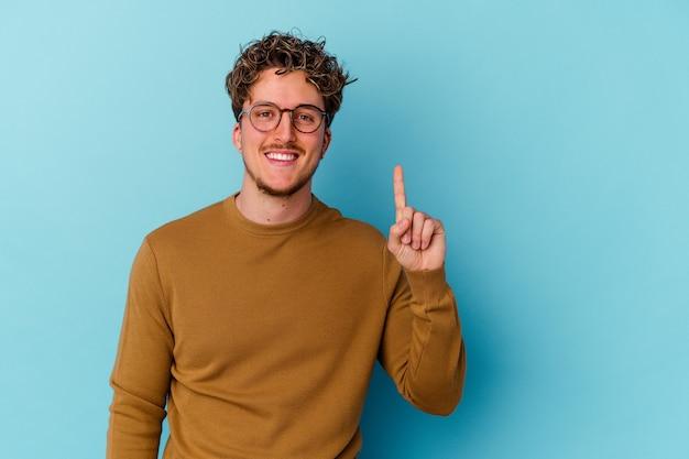 Junger mann, der brillen lokalisiert auf blauer wand trägt, die nummer eins mit finger zeigt