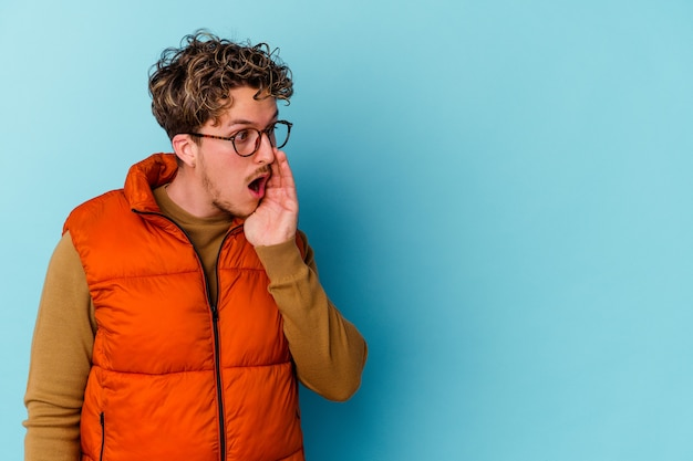 Junger mann, der brillen trägt, die auf blaue wand isoliert werden, sagt eine geheime heiße bremsnachricht und schaut zur seite