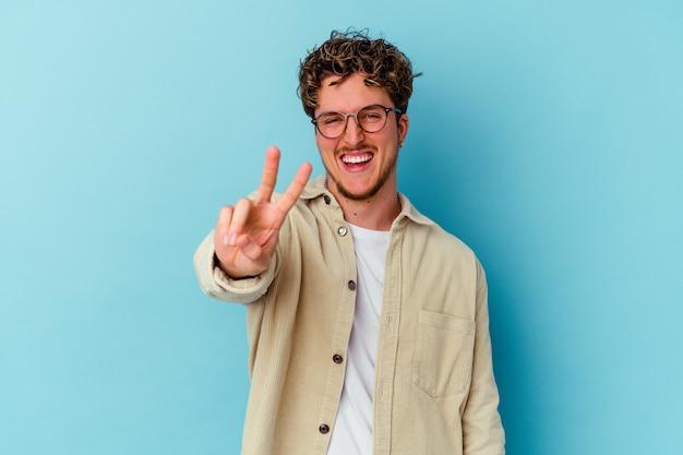 Junger mann, der brillen trägt, die auf blaue wand lokalisiert werden, die nummer zwei mit den fingern zeigt