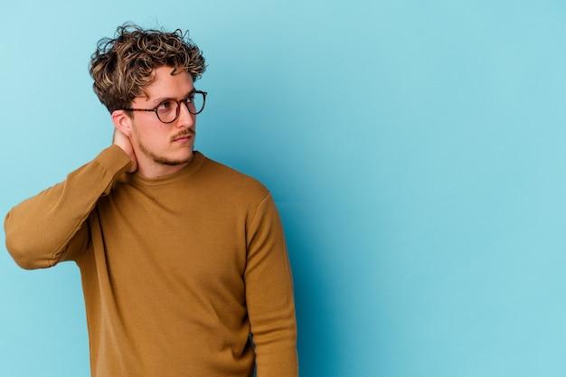 Junger mann, der brillen trägt, die auf blauer wand isoliert sind, die hinterkopf berührt, denkt und eine wahl trifft
