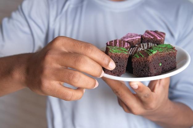 Junger mann, der brownie auf teller isst