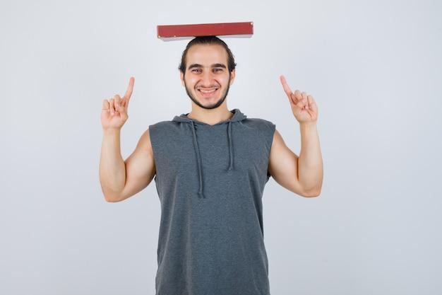 Junger mann, der buch auf kopf hält, während er im ärmellosen kapuzenpulli zeigt und freudig aussieht. vorderansicht.