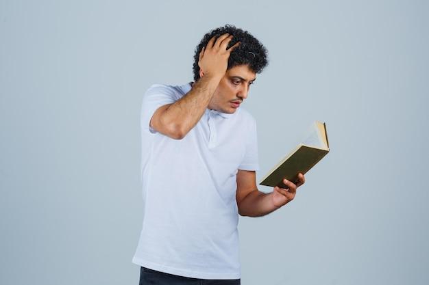 Junger mann, der buch hält und kopf in weißem t-shirt und jeans kratzt und nachdenklich aussieht, vorderansicht.