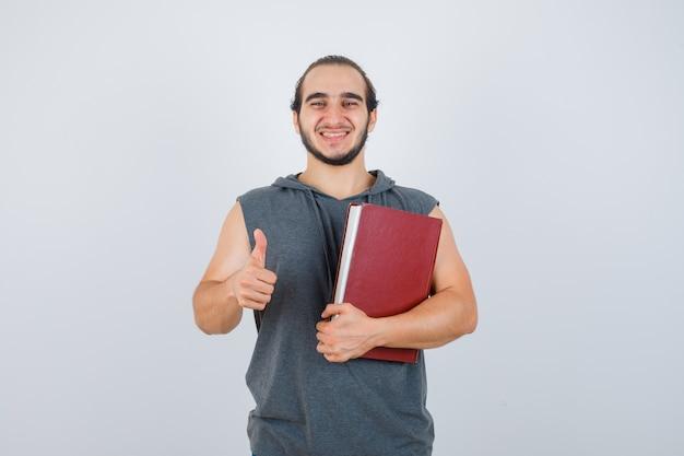 Junger mann, der buch hält, während daumen in ärmellosem kapuzenpulli zeigt und glückliche vorderansicht schaut.