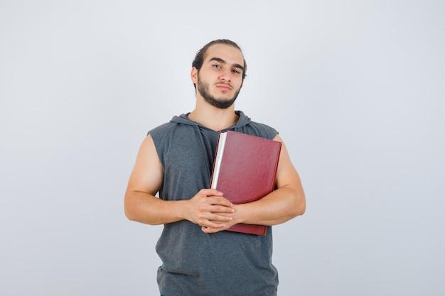 Junger mann, der buch hält, während er im ärmellosen kapuzenpulli aufwirft und selbstbewusst aussieht. vorderansicht.
