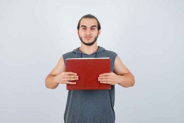 Junger mann, der buch vor ihm im ärmellosen kapuzenpulli hält und ernst aussieht. vorderansicht.