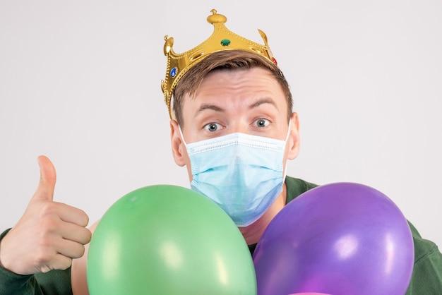 Junger mann, der bunte luftballons in der maske auf weiß hält