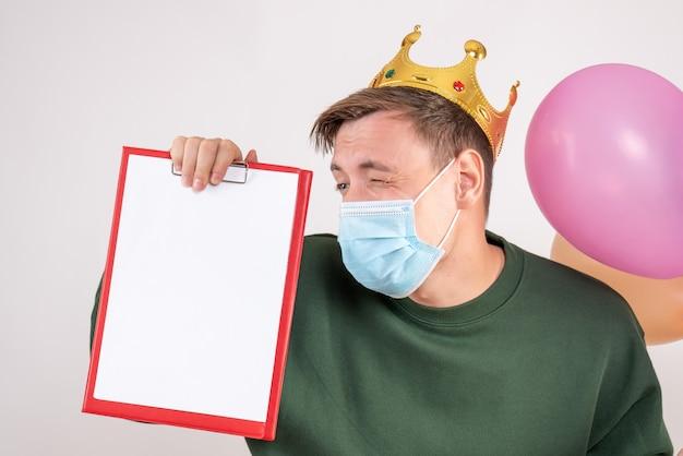 Junger mann, der bunte luftballons und notiz in der maske auf weiß hält