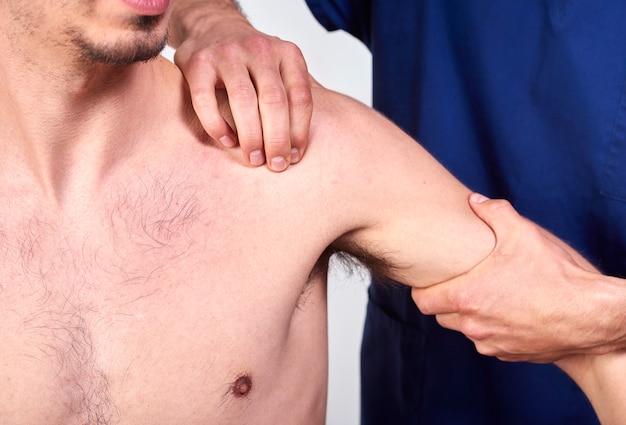 Junger mann, der chiropraktikschultereinstellung hat.