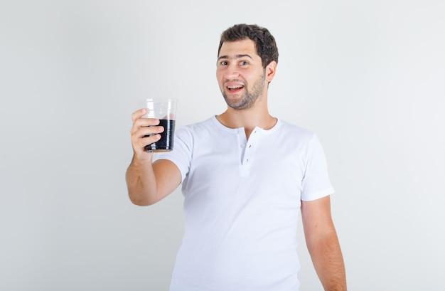 Junger mann, der cola-getränk im weißen t-shirt hält und glücklich schaut