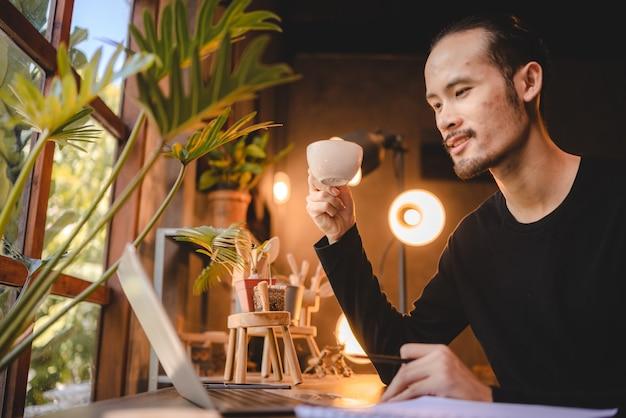 Junger mann, der computer-laptop oder tablet für die arbeit verwendet und online-kommunikation von zu hause aus lernt, cyberspace-bildungstechnologie für geschäftsleute oder studenten, die zur arbeit arbeiten, hipster-geschäftsmann