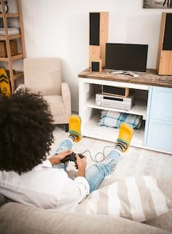 Junger mann, der computerspiele spielt, die zu hause auf der couch vor dem fernsehen sitzen.