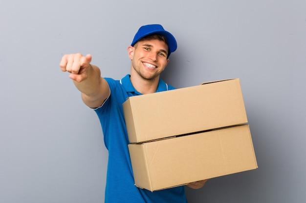 Junger mann, der das freundliche lächeln der pakete zeigt auf front liefert.