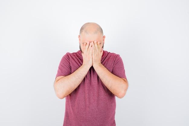 Junger mann, der das gesicht mit den händen im rosa t-shirt bedeckt, vorderansicht.