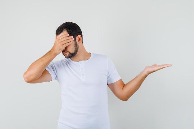 Junger mann, der das gesicht mit der hand bedeckt, während er im t-shirt zur seite zeigt und unzufrieden aussieht, vorderansicht.