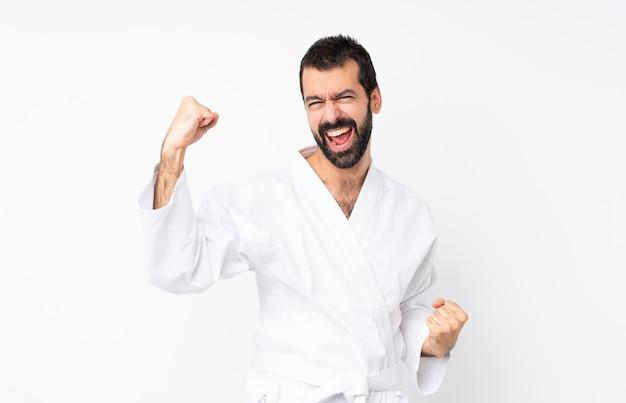 Junger mann, der das karate feiert einen sieg tut
