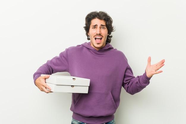 Junger mann, der das pizzapaket feiert einen sieg oder einen erfolg hält