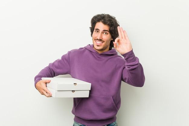 Junger mann, der das pizzapaket nett und überzeugt zeigt okaygeste hält.