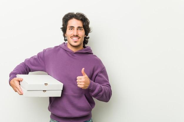 Junger mann, der das pizzapaket oben lächelt und anhebt daumen hält