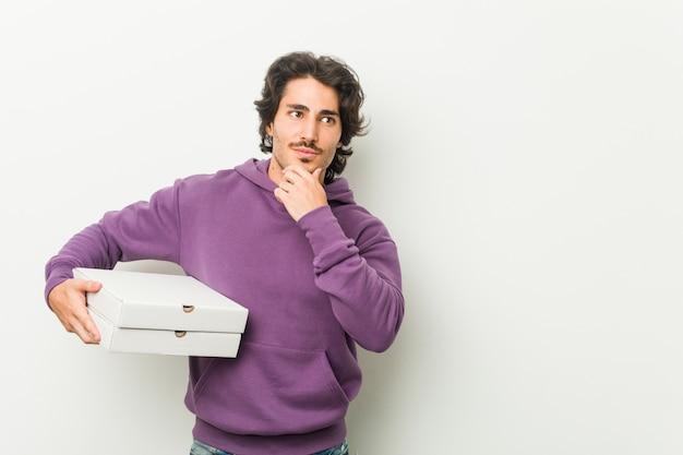 Junger mann, der das pizzapaket seitlich schaut mit zweifelhaftem und skeptischem ausdruck hält.