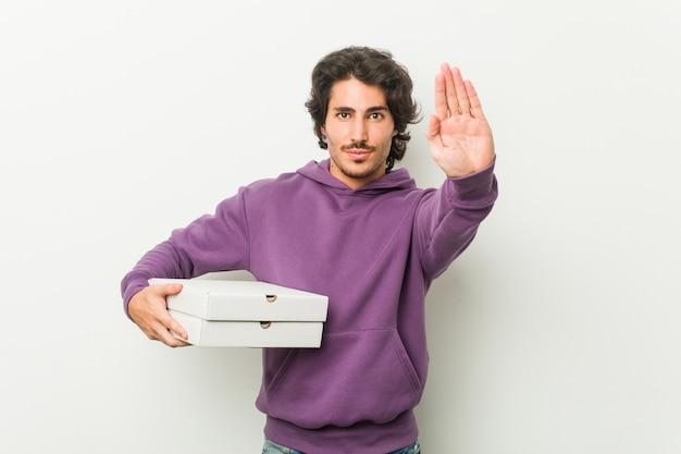 Junger mann, der das pizzapaket steht mit der ausgestreckten hand zeigt das stoppschild, sie verhindernd hält.