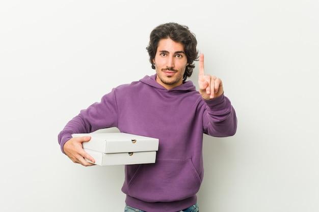 Junger mann, der das pizzapaket zeigt nummer eins mit dem finger hält.