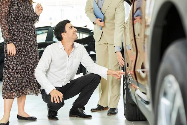Junger mann, der das rad des neuen autos untersucht und mit manager spricht, während autoausstellungsraum mit frau besucht